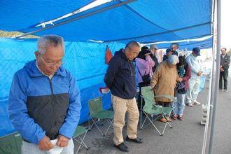 俳優の故菅原文太さんに黙とうをささげる市民ら=2日午前9時半ごろ、名護市辺野古・米軍キャンプ・シュワブのゲート前