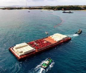 沖縄県名護市辺野古の沿岸部に到着した、コンクリート製ブロックを積んだ台船。奥は米軍キャンプ・シュワブ=5日(小型無人機から)