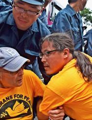 仲間とスクラムを組み、座り込むウィル・グリフィンさん(右)=5日午前10時55分、東村高江