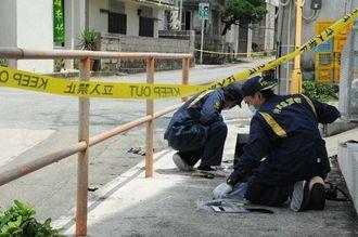 被害者のものと見られる血痕などを調べる県警の鑑識課員=久米島町鳥島(比嘉正明通信員撮影)