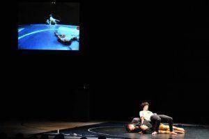 舞台上のカメラで映し出された映像と登場人物3人の動きが重なり不思議な空間が広がった=国立劇場おきなわ