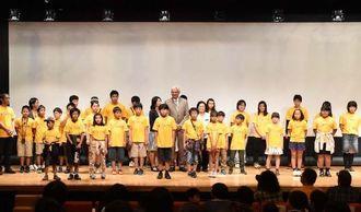 オープニングで舞台に勢揃いした子どもスタッフ=22日、那覇市・県立博物館・美術館講堂