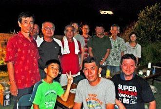 新里区の山に浮かぶ光文字「20里」と、作業した仲本直樹さん(前列中央)ら=24日、南城市の同区