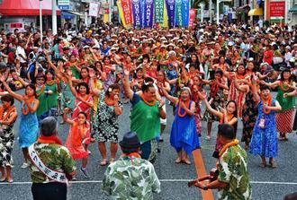 フラダンスを踊るハワイ沖縄連合会のメンバー=那覇市牧志・国際通り(下地広也撮影)