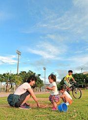 青空の下、砂遊びをする子ども=16日、那覇市おもろまち・新都心公園