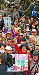 登壇者のあいさつに気勢を上げる集会参加者=29日午後、那覇市楚辺・城岳公園