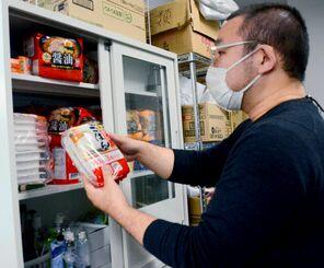 年末年始を前に備蓄食料を整理する相談支援員の和田聡さん=25日、那覇市泉崎の県就職・生活支援パーソナルサポートセンター南部支所