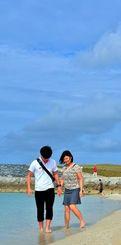 青空が広がるビーチではだしで波打ち際を歩く観光客=21日午後、宜野湾市・トロピカルビーチ