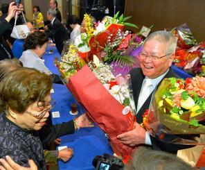 関係者から花束を贈られ喜びを分かち合う受賞者(右側)=23日、沖縄かりゆしアーバンリゾート・ナハ(古謝克公撮影)