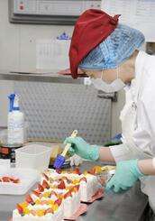 フラッシュパークの自社工場でケーキを完成させる女性スタッフ=東京都大田区