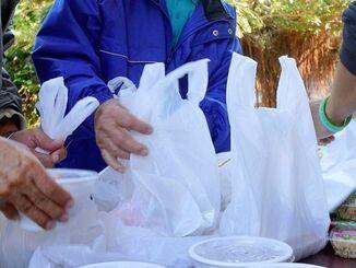 炊き出しで無償で中味汁などを受け取る人たち=2日、那覇市の与儀公園