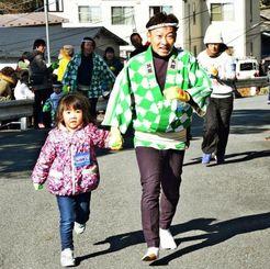 手をつないで、高台の寺院までの坂道を駆け上がる親子=2月7日、岩手県釜石市