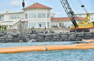 N5護岸建設に向け、砕石を海へ投下する作業員=6日10時39分、名護市辺野古