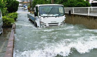 冠水した道路を水しぶきを上げて走るトラック=午後2時8分、糸満市潮平(下地広也撮影)
