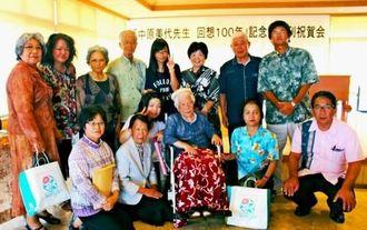 中原さん(前列右から3人目)を囲んで出版を祝う教え子とその保護者ら=16日、伊江村