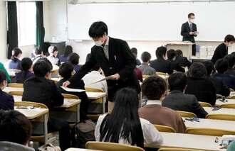 大学入学共通テストの問題用紙を配布する試験官=16日午前9時すぎ、西原町・琉球大学