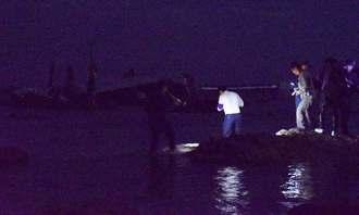 大破したオスプレイの機体(奥)を撮影するため詰め掛ける報道陣ら=14日午前2時38分、名護市安部の海岸