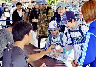 お目当ての選手からサインをもらい笑顔を見せる子どもたち=1日、ぎのわん海浜公園(下地広也撮影)