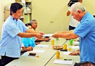 新里米吉座長(右)から参院選の立候補要請を受ける伊波洋一氏=24日、宜野湾市野嵩