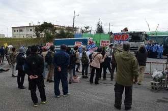 工事関係車両に向けて「違法な工事はやめろ」とプラカードで訴える市民ら=12日、名護市辺野古の米軍キャンプ・シュワブゲート前
