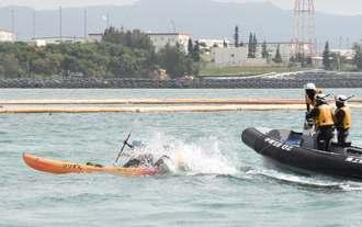 抗議のカヌーを拘束するため海に飛び込む海上保安官=26日午前、米軍キャンプ・シュワブ沖
