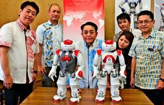 人型ロボット「NAO」を囲む琉球ネットワークサービスの上原会長(中央)ら=19日、沖縄県庁