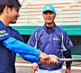 打撃練習の選手にアドバイスをするエナジックの石嶺和彦監督(右)=名護市営球場(山城知佳子撮影)