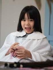 切った髪の長さに驚く松本結心さん=3日、宜野湾市の美容室「dunno」