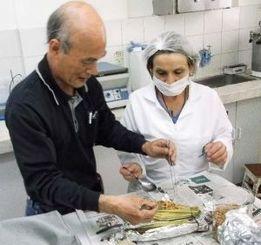 研究室での納豆づくりを指導する外間数男さん(左)=ボゴタ市