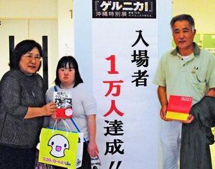 1万人目の来場者となった(左から)大木悠子さん、麻里さん、修さん家族=12日、県立博物館・美術館