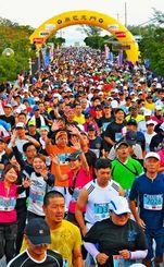 ドラの合図で一斉にスタートするハーフマラソンの参加者=2日午前9時すぎ、南城市佐敷のシュガーホール前(古謝克公撮影)