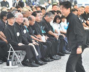 来賓あいさつを終え席へ戻る安倍晋三首相(右)。左は翁長雄志知事=2018年6月23日午後、糸満市・沖縄平和祈念公園
