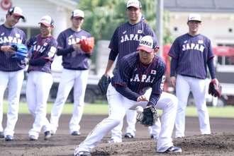 守備練習する侍ジャパンの投手陣=28日午前、奥武山公園の多目的広場(下地広也撮影)