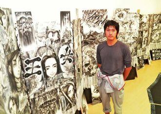 「歩いて読むマンガ」の展示会を開いている竹井友輝さん=26日、那覇市の県立博物館・美術館