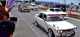 海中道路の一部を使い、右側通行で旧車を走らせる参加者=29日、うるま市