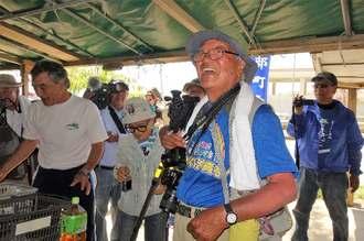 米軍キャンプ・シュワブゲート前を訪れ、基地建設に抗議する人々に出迎えられる石川文洋さん=24日午前11時すぎ、名護市辺野古