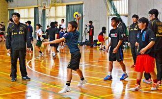 山城貴志選手(左)にアドバイスをもらって練習をするハンドボール部員=1日、浦西中