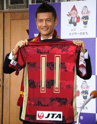 FC琉球に入団し、背番号11のユニホームを披露する播戸竜二=沖縄市役所