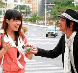 街頭で女性にシークワァサーを手渡し「村コン」を猛アピールした田港区青年会=28日、那覇市・パレットくもじ前