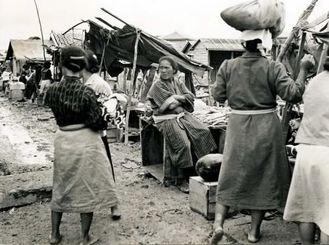 テントを張った掘っ立て小屋、地面に並べられた箱、この粗末なヤミ市場から那覇の公設市場は発展した=1946年ごろ