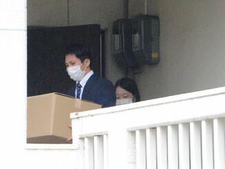 浦添市のめぐみ創研を家宅捜索し、押収品を運び出す捜査員ら=4日、浦添市内