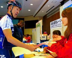 受け付けでゼッケンを受け取る参加者=13日、恩納村コミュニティセンター