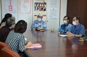 追悼式の会場変更について、担当部局の職員(左)に意見を伝える「沖縄全戦没者追悼式のあり方を考える県民の会」のメンバーら=2日、県庁