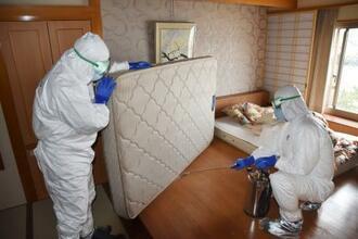 客室の布団に消毒液を吹きかける防護服姿の作業員=16日午後、千葉県勝浦市の「勝浦ホテル三日月」
