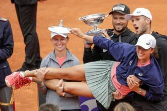 テニスのイタリア国際で今季2勝目を挙げ、抱きかかえられて祝福を受けるイガ・シフィオンテク=16日、ローマ(AP=共同)