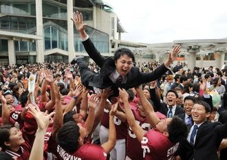 琉球大学の後輩から胴上げされる卒業生=18日午後、宜野湾市の沖縄コンベンションセンター