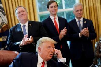 ホワイトハウスの執務室で、スーダンのテロ支援国家指定解除について通話するトランプ大統領=23日、ワシントン(ロイター=共同)