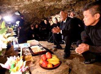 チビチリガマの中で手を合わせる與那覇徳市さん(右から2人目)=7日午後、読谷村波平のチビチリガマ(代表撮影)