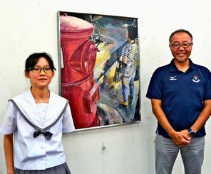 受賞作品を背に抱負を語る松下桜さん(左)と伊元隆一教諭=開邦高校