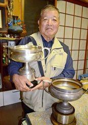 見つかった島田杯を抱きかかえる県高野連の安里嗣則元理事長。手前は現在使われている島田杯=17日、沖縄市泡瀬